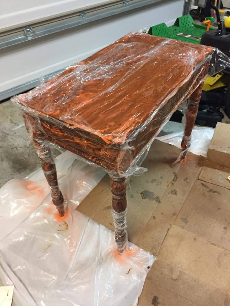 wrapping the furniture with saran wrap after applying the wood stripper