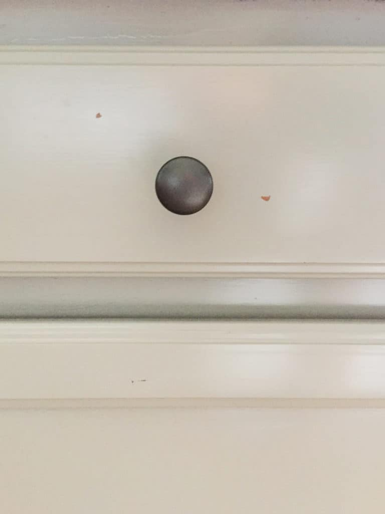 scratches around the knob of the laminate cabinets