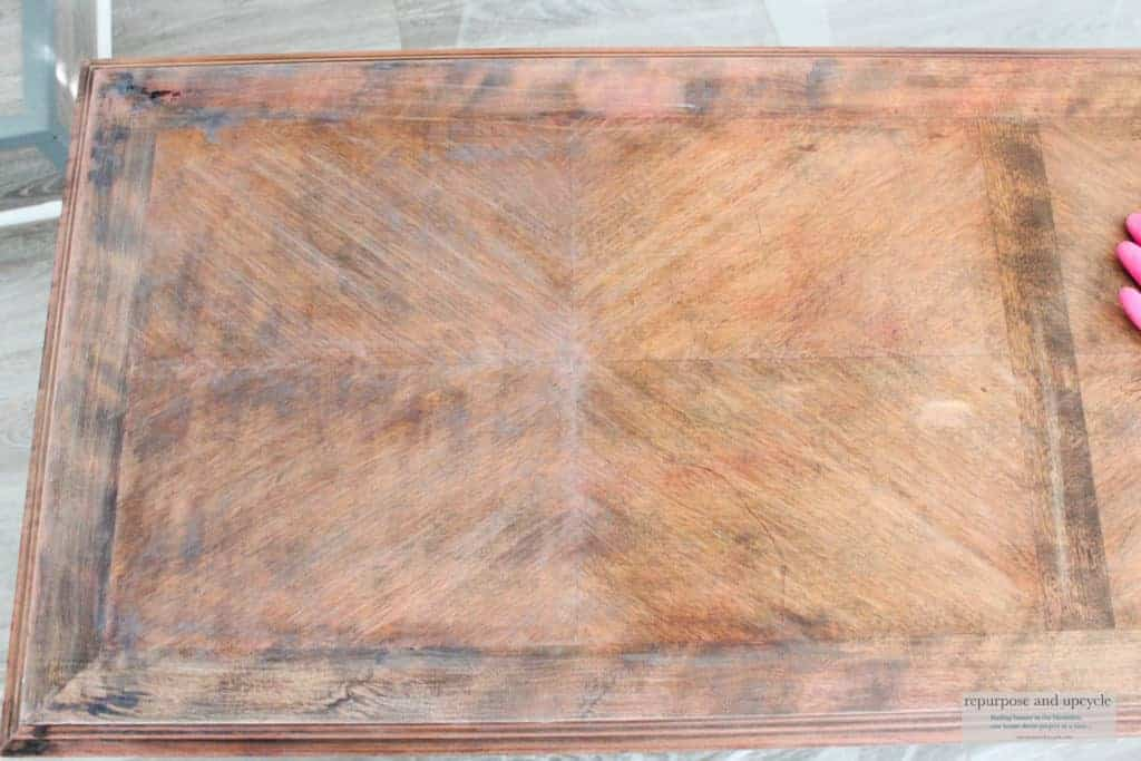 Applying liming wax to a coffee table