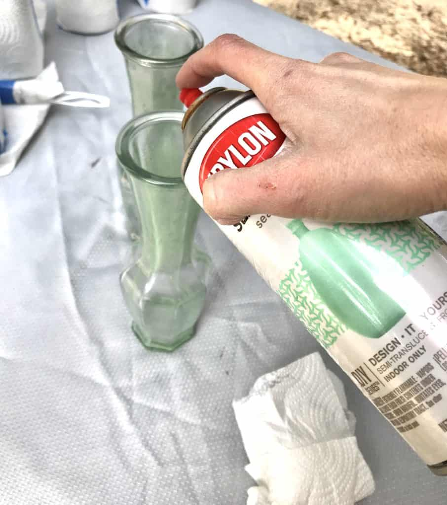 applying Krylon sea glass spray paint to glass vase