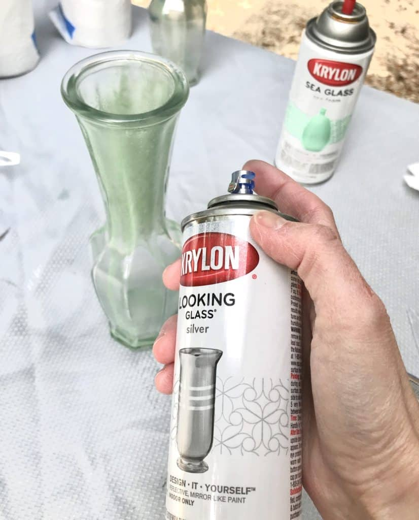 applying looking glass spray paint to glass vase