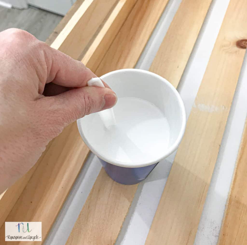 stirring the diluted paint mixture for whitewashing bare wood
