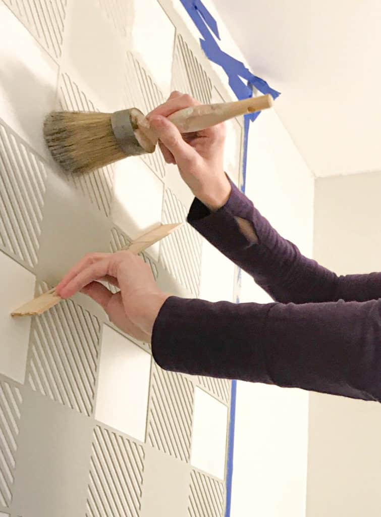 applying paint to the wall with the stencil