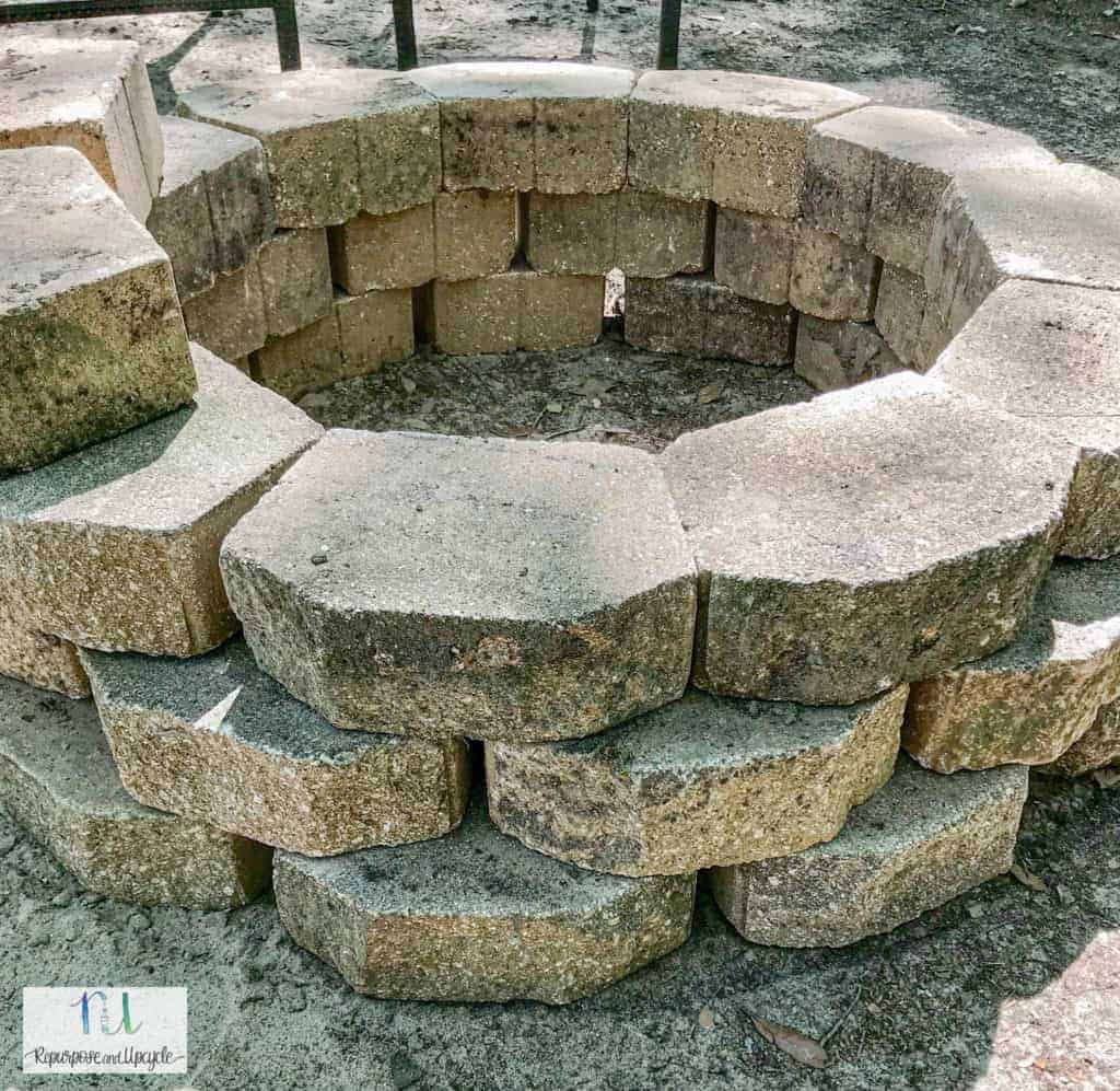 Placing rows of concrete pavers for fire pit