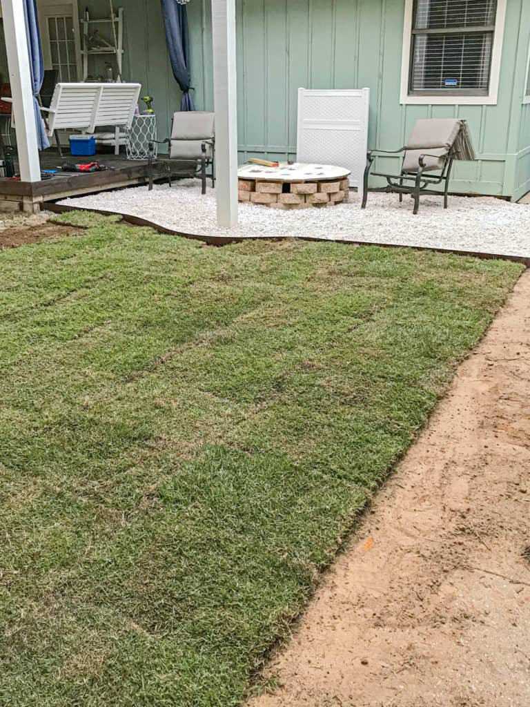 laying sod around the gravel patio