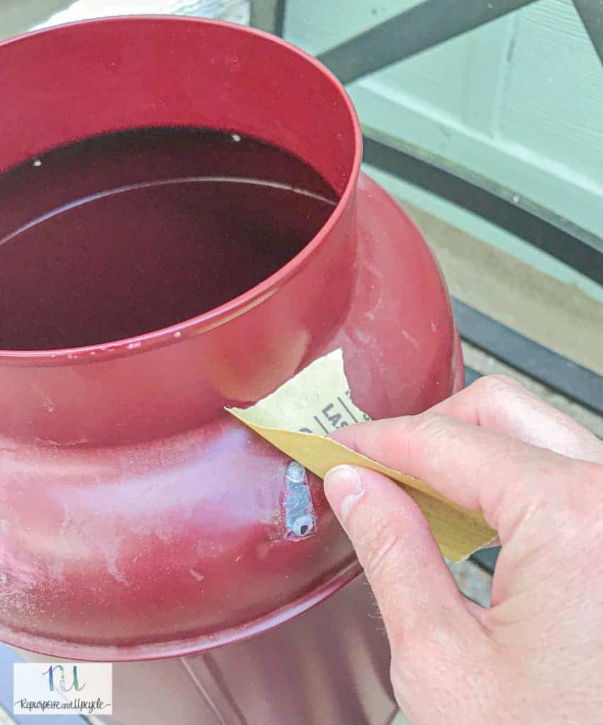 sanding the vintage milk can