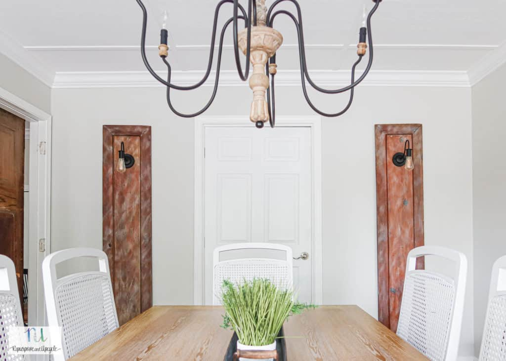 cottage style dining room with sconce lights