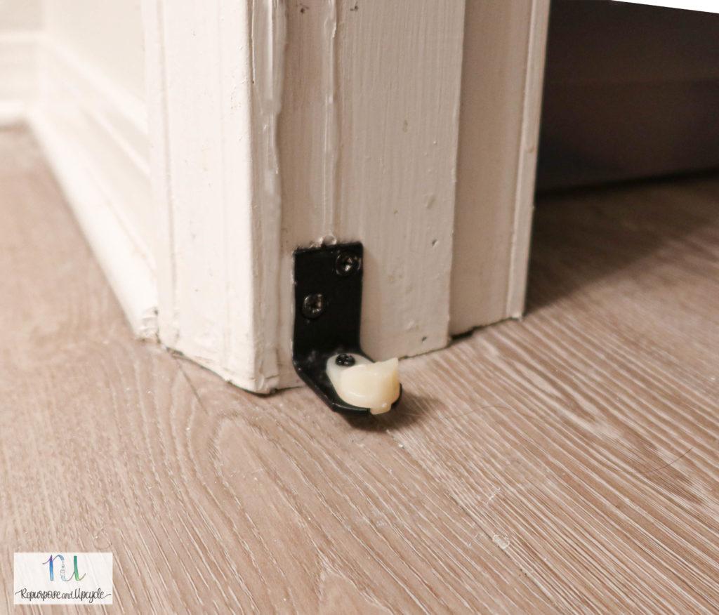 Installed cafe door hardware for the bottom doorframe