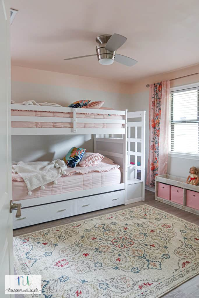 girls bedroom with pink ceiling and white bunk beds
