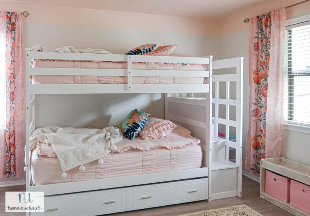 white bunk beds with pink zipper bedding
