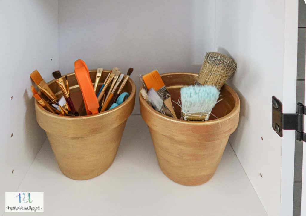 paint brushes organized in a craft cabinet