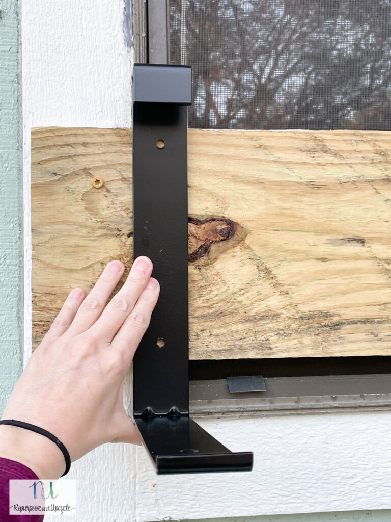 planter box hardware installed on wood on top of a window