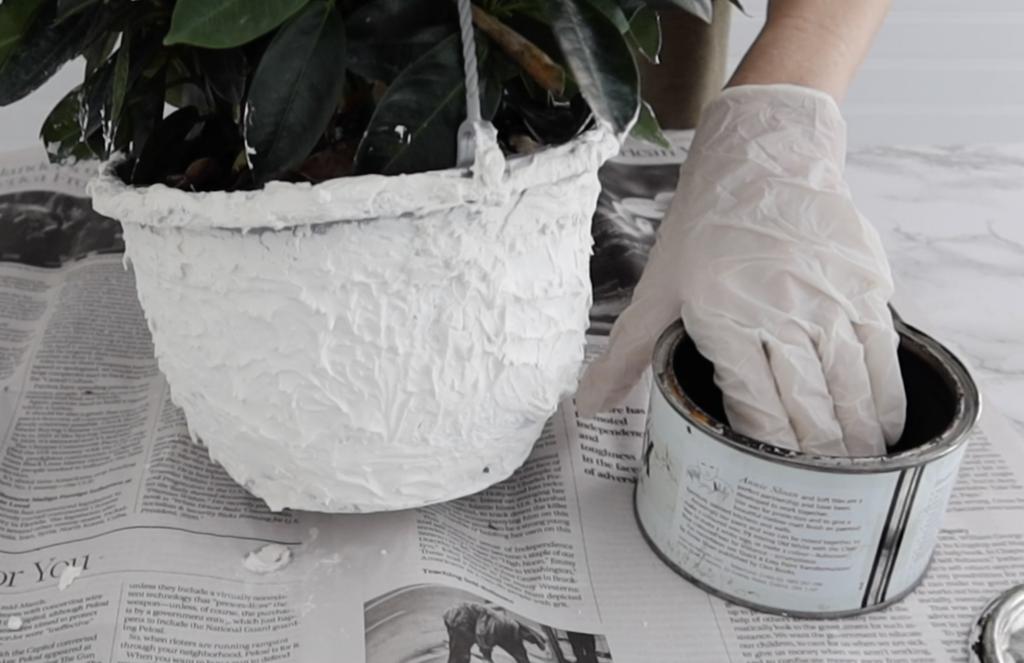 applying dark wax to textured pot