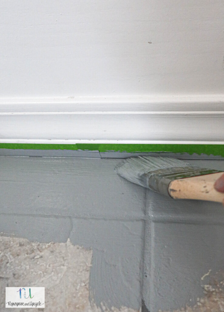 using paintbrush to cut in to the edges of the tile
